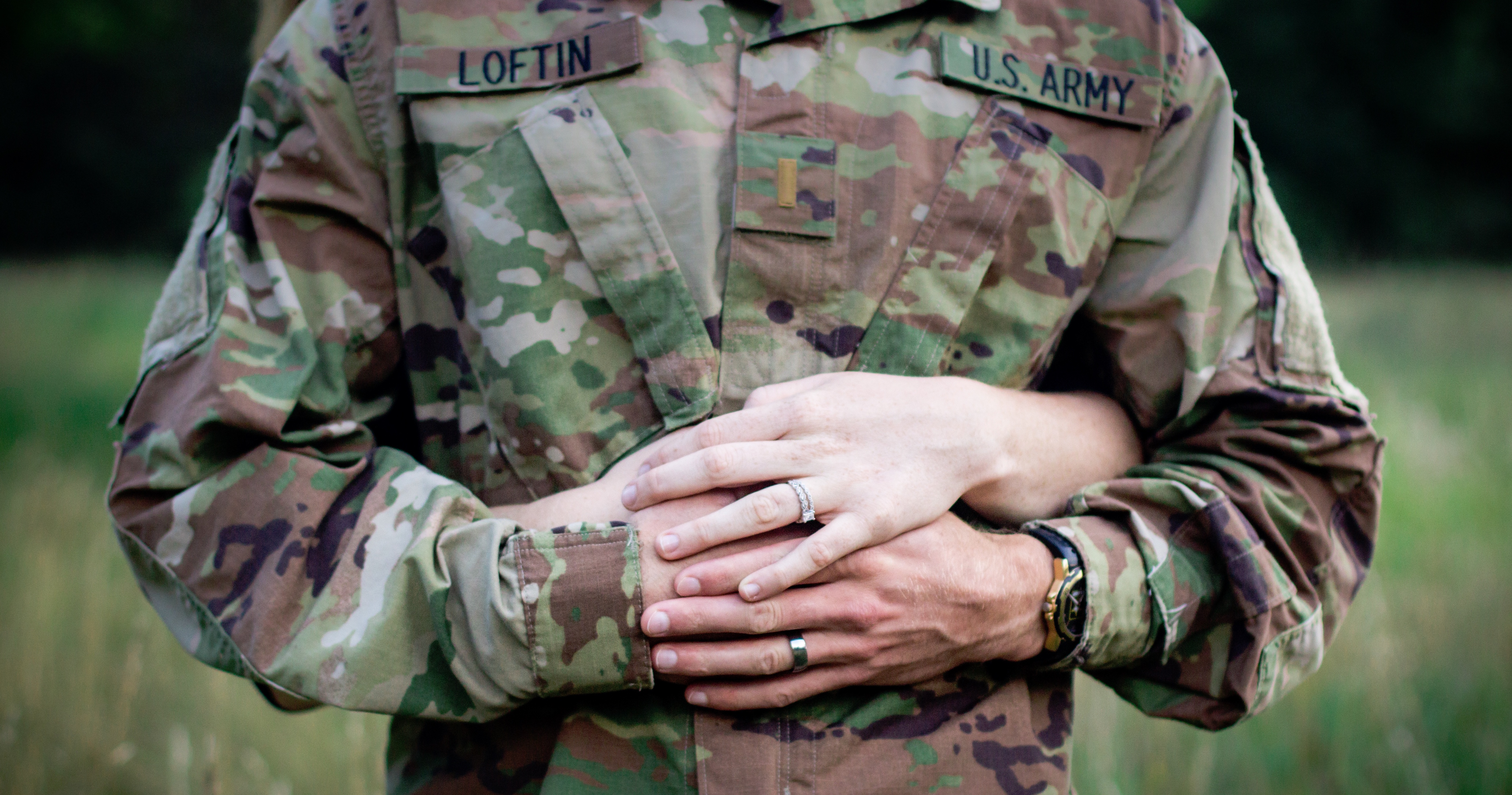 A military couple embrace each other and display their sparkling wedding bands