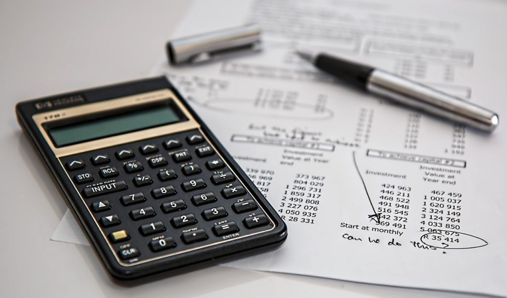 A photo of a calculator and finance papers