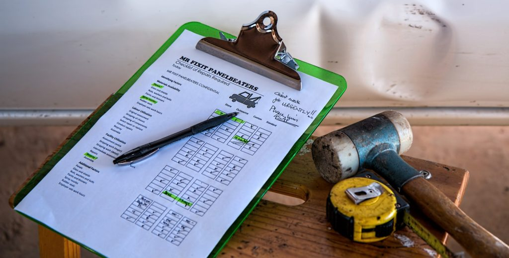 A photo of a checklist of home improvements sitting next to a hammer and tape measurer