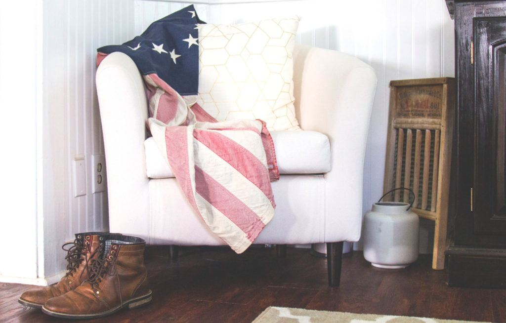 Photo of an American flag laying over a chair inside a home