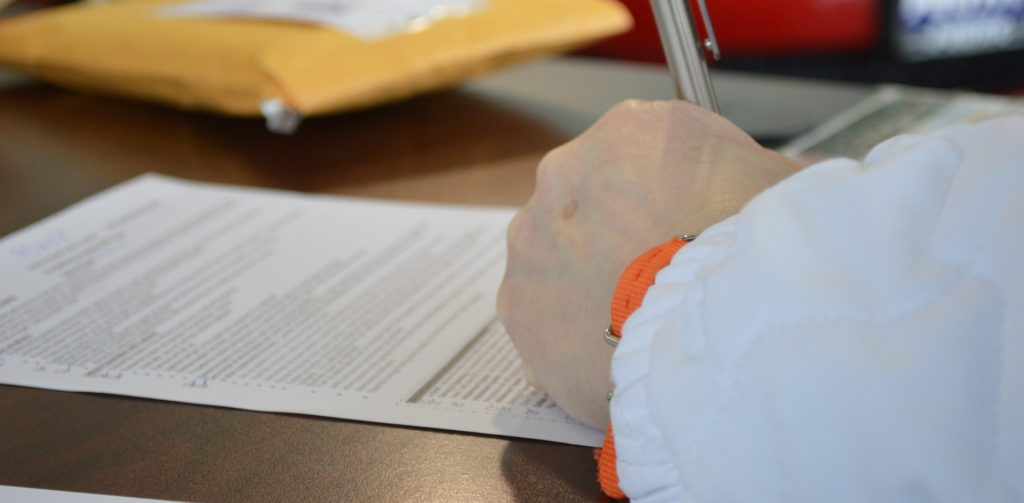 A photo of someone signing a document